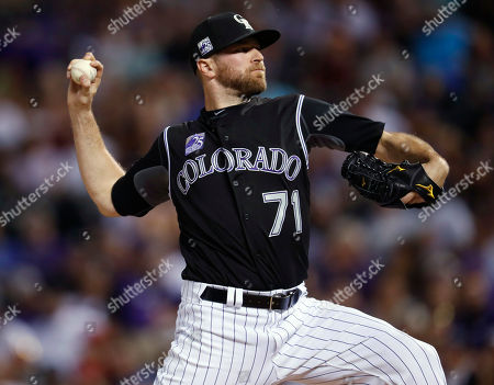 Colorado Rockies relief pitcher Wade Davis delivers a pitch to Cincinnati Reds' Billy Hamilton during the ninth inning of a baseball game, in Denver. The Rockies won 5-4