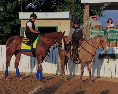Kentucky Derby and Preakness Stakes champion Justify, left, with exercise rider Humberto Gomez in the saddle, waits to enter the track at Churchill Downs in Louisville, Ky., for a morning gallop. Assistant trainer Jimmy Barnes, right, leads the colt as preparations continue for Justify's possible Triple Crown bid in the 150th Belmont Stakes in New York in June