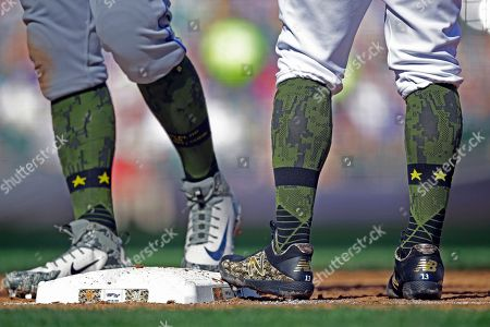 Milwaukee Brewers' Tyler Saladino, right, and New York Mets' Adrian Gonzalez wear camouflage socks for the Memorial day weekend during the third inning of a baseball game, in Milwaukee