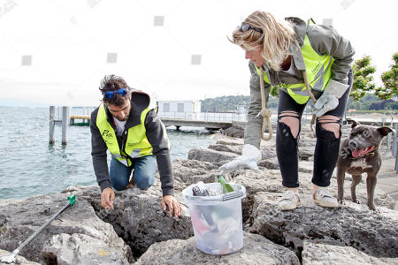 Switzerland's skipper Alan Roura, and his girlfriend Aurelia Mouraud, next to their dog Louna, collect garbage in the Geneva harbor of the Lake of Geneva during the ninth edition of the 'Net'Leman' lake cleaning event, in Geneva, Switzerland, 27 May 2018. Over a thousand volunteers took part in the annual lake cleanup event.