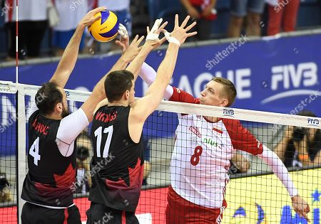 Stock Photo of Damian Schulz (R) of Poland in action against Nicholas Hoag (L) and Graham Vigrass (C) of Canada during FIVB Volleyball Nations League tournament and match between Poland and Canada in Krakow, Poland, 27 May 2018.