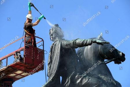 Russia, St. Petersburg, May 26, 2018.  A utility worker washing Bronze Horseman, an equestrian statue of Peter the Great by French sculptor Etienne Maurice Falconet, in Senate Square.