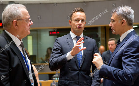 Hungarian Foreign Minister Peter Szijjarto, center, speaks with Malta's Foreign Minister Carmelo Abela, right, and European Commissioner for International Cooperation Neven Mimica during a meeting of EU foreign ministers at the Europa building in Brussels on . EU foreign ministers on Monday were seeking to protect the bloc's strategic and economic interests in Iran in the wake of the U.S. withdrawal from the international nuclear deal