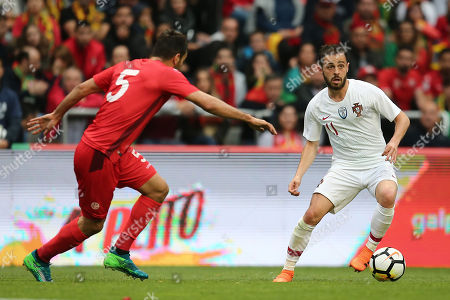 Bernardo Silva (R) of Portugal fights for the ball with Tunisia player Oussama Haddadi during the friendly soccer match between Portugal and Tunisia in Braga, Portugal, 28 May 2018.