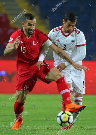 Turkey's Mehmet Topal, left, fights for the ball with Iran's Ehsan Hajsafi, right, during a friendly soccer match between Turkey and Iran, in Istanbul