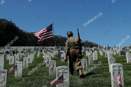 Stock Photo of David Proud, a World War II historian, walks among veterans gravestones during an observance for Memorial Day at San Francisco National Cemetery in the Presidio in San Francisco