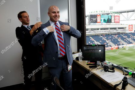 Stock Image of Fox Sports broadcasters Stuart Holden, left, and John Strong put on their coats for a photo before an international friendly soccer match between the United States and Bolivia, in Chester, Pa