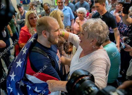Josh Holt, left, is draped in an America flag by his grandmother, Linda Holt, upon returning to Salt Lake City, as he was freed this weekend after being held in a Venezuelan jail for nearly two years. He returned home to Salt Lake City on Monday night after getting medical care and visiting President Donald Trump in Washington