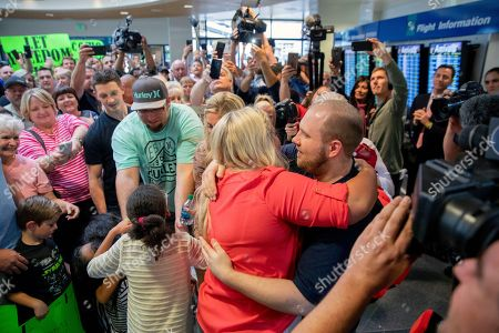 Josh Holt, right, is greeted by family and friends upon returning to Salt Lake City, after receiving medical care and visiting President Donald Trump in Washington. Holt was freed this weekend after being held in a Venezuelan jail for nearly two years