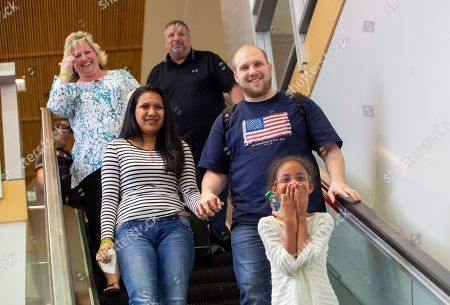 Josh Holt, right, returns with wife, Thamara Caleno, left, and daughter, Marian, bottom, to a crowd of friends and family in Salt Lake City after receiving medical care and visiting President Donald Trump in Washington on . Holt and his wife were freed this weekend after being held in a Vfenezuelan jail for nearly two years. Holt's parents Laurie and Jason Holt stand in the background