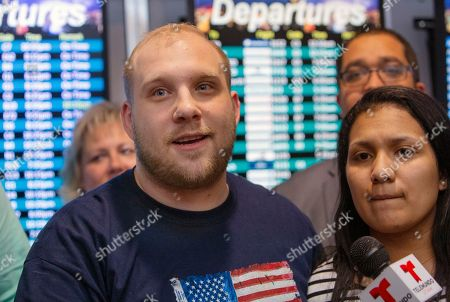 Stock Photo of Josh Holt, left, makes a statement to the media with his wife, Thamara Caleno, right, upon their arrival in Salt Lake City after receiving medical care and visiting President Donald Trump in Washington on . Holt, and his Venezuelan wife were locked in a Caracas jail alongside some of the country's most-hardened criminals - and President Nicolas Maduro's top opponents - for what the U.S. government argued were bogus charges of stockpiling weapons