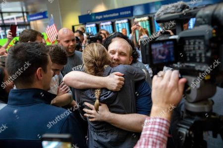 Stock Picture of Josh Holt, middle, is greeted by family and friends upon returning to Salt Lake City after receiving medical care and visiting President Donald Trump in Washington on . Holt was freed this weekend after being held in a Venezuelan jail for nearly two years