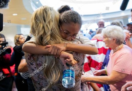 Josh Holt's daughter, Marian, center right, is hugged by her aunt Jenna Nemeth at Salt Lake City International Airport, in Salt Lake City. Marian arrived with her father and stepmother from Caracas, Venezuela. Josh Holt and his wife were released from a Venezuelan jail over the weekend, after being imprisoned for nearly two years