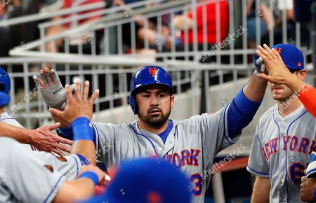 New York Mets' Adrian Gonzalez is congratulated after hitting a solo home run during the fourth inning of the team's baseball game against the Atlanta Braves, in Atlanta