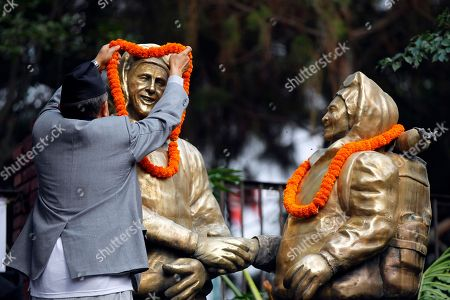 A man puts a garland around the statues of New Zealander Edmund Hillary, left, and his Sherpa guide Tenzing Norgay, who became the first climbers to reach the top of 8,850-meter (29,035-foot) Everest on May 29, 1953 in Kathmandu, Nepal, . Nepal has honored several Sherpa guides for their own Everest successes on the anniversary of the first conquest of the world's highest peak