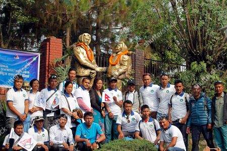 Nepalese mountain climbers pose in front of the statues of New Zealander Edmund Hillary, and his Sherpa guide Tenzing Norgay during a function organized to mark Everest Day in Kathmandu, Nepal, . Nepal has honored several Sherpa guides for their own Everest successes on the anniversary of the first conquest of the world's highest peak