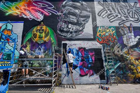 Street artists (L to R) Jim Vision and Core246 at work at 'Meeting of Styles' near Brick Lane in East London. The three day festival celebrates street art, with artists from around the world demonstrating their skills.