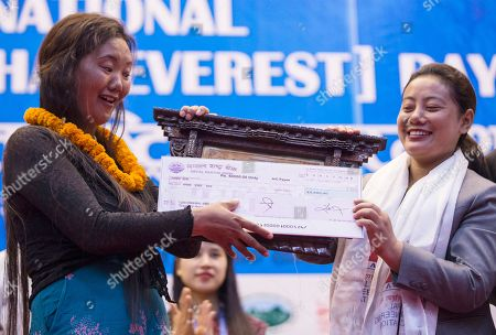 Nepalese Minister of water supply Bina Magar felicitates Lhakpa Sherpa, aged 44, with Tenzing Hillary Mountaineering Award during the function to mark the International Everest Day in Kathmadu, Nepal, 29 May 2018.  Lhakpa Sherpa has successfully climbed Mount Everest 9 times, setting a new world record for the most ascents of Mount Everest by a woman. Nepal is celebrating the 'International Everest Day' with various events on 29 May 2017 commemorating the first climb to the summit on 29 May 1953 by Sir Edmund Hillary and Tenzing Norgay Sherpa.