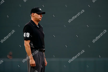 Umpire Andy Fletcher stands in the infield during an interleague baseball game between the Baltimore Orioles and the Washington Nationals, in Baltimore