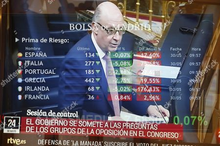 Multiexposure of a TV news picturing Spanish Treasure Minister, Cristobal Montoro, and a screen displaying several European risk premium figures at Madrid Stock Exchange Market, Spain, 30 May 2018. The index IBEX 35 rose by 0.15 percent at the opening of the trading day to reach 9,535.90 points helped by banking sector, a day after the Spanish stock market fell around 2.5 percent due to political instability in Italy and Spain.