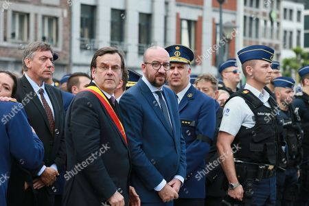 Belgian Prime Minister Charles Michel (C) and Leige City Mayor Willy Demeyer (C-R) together with police officers take part in a minute of silence for the victims of the shooting that took place a day earlier, in Liege, Belgium, 30 May 2018. On 29 May, a gunman was shot dead by anti-terrorist police after reportedly killing two police officers and a passerby and injuring two others in the center of the Belgian city of Liege. During a shootout the man was said to have entered a high school where he took a female cleaner hostage before being shot by the police.