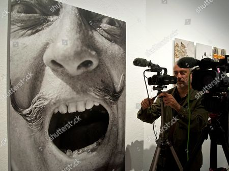 A cameraman works next to a portrait of Spanish artist Salvador Dali during the presentation of a photo exhibition of British photographer Robert Whitaker at the Theatre-Museum in Figueres, Spain, 30 May 2018. The exhibition titled 'Salvador Dali. Robert Whitaker. 1967-1972' features 27 portraits of Dali made in the village of Porlligat and Paris.