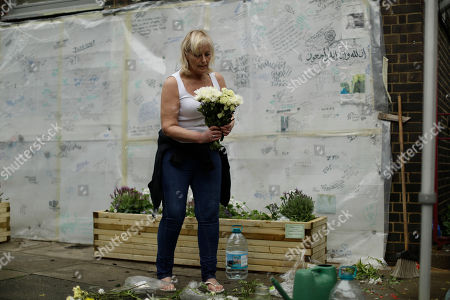 Local resident Theresa Griffin arranges and places flowers beside a tribute wall near Grenfell Tower, almost one year on from the fire that killed 72 people, in London, . London has been gripped by the accounts of friends and relatives of the 72 victims of the inferno at Grenfell Tower almost a year ago. A public inquiry seeks to establish what led up to the fire and make recommendations to prevent a similar tragedy, but the litany of pain will leave an impression not easily forgotten