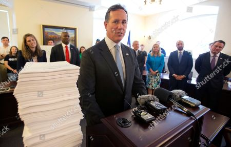 Former US Senator Rick Santorum stands next to a stack of letters and emails from people opposed to Medicaid Expansion during a press conference at the Capitol in Richmond, Va., . The Senate is due to vote son a budget proposal today
