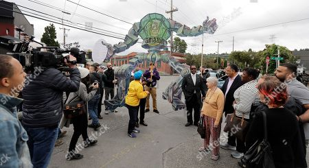 Protesters hold a sign depicting Amazon.com founder and CEO Jeff Bezos as a mechanical robot as they stand outside Amazon's annual meeting of shareholders, in Seattle. Onlookers included the Rev. Jesse Jackson, fourth from right, who has been outspoken about the need for better minority representation in high tech hiring, who was in town to attend the meeting