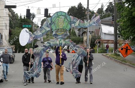 Protesters march with a sign depicting Amazon.com founder and CEO Jeff Bezos as a mechanical robot as they walk near Amazon.com's annual meeting of shareholders, in Seattle. Protesters were seeking union representation and better pay for Amazon workers as well as more attention to environmental and other issues from the online retailer