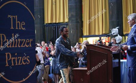 """Pulitzer Prize winner for music Kendrick Lamar, left, extends his hand to Columbia University President Lee Bollinger, right, as he accepts award for the album """"DAMN,"""" during the 2018 Pulitzer Prize awards luncheon at Columbia University, in New York"""