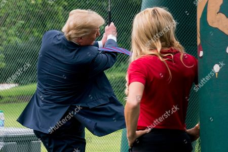 Stock Photo of Donald Trump, Natalie Gulbis. Golfer Natalie Gulbis, right, watches as President Donald Trump swings a golf club during White House Sports and Fitness Day on the South Lawn of the White House, in Washington