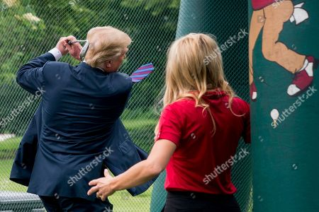 Donald Trump, Natalie Gulbis. Golfer Natalie Gulbis, right, watches as President Donald Trump swings a golf club during White House Sports and Fitness Day on the South Lawn of the White House, in Washington
