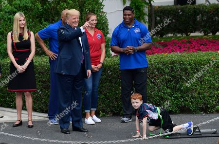 Stock Photo of Donald Trump, Herschel Walker, Mariano Rivera, Misty May-Treanor. President Donald Trump waits to start a race during the White House Sports and Fitness Day event on the South Lawn of the White House in Washington, . Trump is joined by, from left, Ivanka Trump, former New York Yankees relief pitcher Mariano Rivera (partially hidden), beach volleyball star Misty May-Treanor, and football star Herschel Walker