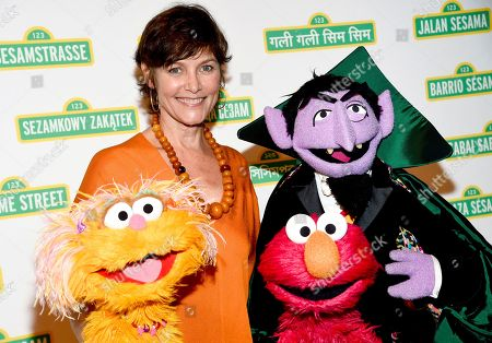 Actress Carey Lowell poses with Zoe, Elmo and The Count at Sesame Workshop's 16th annual Benefit Gala at Cipriani 42nd Street, in New York