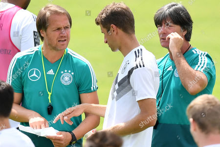 Stock Photo of German coaches Thomas Schneider (L) and Joachim Loew (R) talk to Germany's Thomas Mueller (C) during a training session in Eppan, Italy, 31 May 2018. The German squad prepares for the upcoming FIFA World Cup 2018 soccer championship in Russia at a training camp in Eppan, South Tyrol, until 07 June 2018.