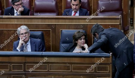 Spanish Deputy Prime Minister, Soraya Saenz de Santamaria (C), chats with one of her party's MPs next to Foreign Affairs Minister Alfonso Dastis, shortly before the no confidence motion debate against Prime Minister, Mariano Rajoy, resumes at the Lower House of Spanish Parliament, in Madrid, Spain, 31 May 2018. Socialist Party's leader Pedro Sanchez (unseen) filed the motion last 25 May, a day after former PP officials were found guilty in the so-called Guertel corruption trial. Sanchez's motion needs to be backed in the two-day debate with half plus one of the 350 deputies' votes to be successful. If so and Sanchez gets the support from other parties, with Basque PNV party's ones absolutely indispensable, he would unseat Rajoy and call snap elections in a future date to be agreed on by the opposition parties. This one is the second confidence vote thant Rajoy faces in a year.
