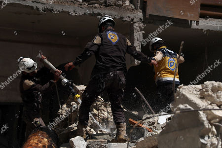 Stock Image of Syrian firefighters and civil defense personnel work at the site of explosion at a building in the town of Ariha, Idlib province, Syria, 31 May 2018. According to local reports, three people were killed in an explosion that destroyed a multi-sotrey building in Ariha town of Idlib. The reason of the explosion is still unknown.