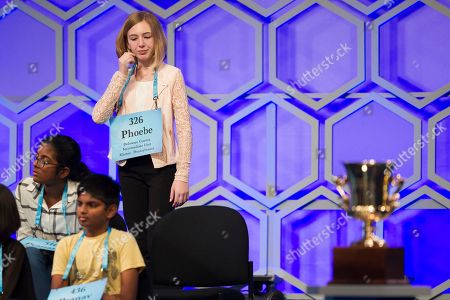 Phoebe Smith, 12, from Aston, Pa., stands near the Champion's Trophy while waiting to spell her word during the finals of the Scripps National Spelling Bee in Oxon Hill, Md