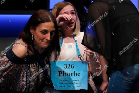 Phoebe Smith, 12, from Aston, Pa., center, is comforted by family and friends after being eliminated during the evening finals of the Scripps National Spelling Bee in Oxon Hill, Md