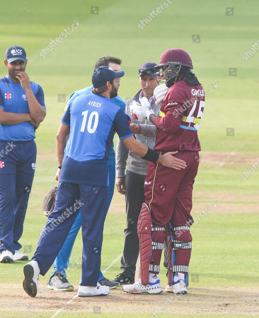 Chris Gayle of the West Indies is hit straight on the helmet visor by Tymal Mills of the ICC World XI short ball Shahid Afridi (Captain) checks he's ok