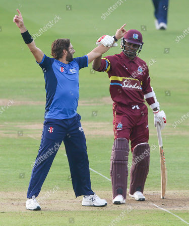 Shahid Afridi (Captain) celebrates the wicket of Andre Fletcher of the West Indies out for 7 runs  stumped Luke Ronchi of the ICC World XI - Marlon Samuels of the West Indies does not look pleased pulling his arm down (R)