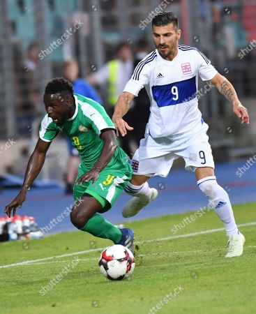 Senegal's Mame Biram Diouf, falls while being chased by Luxembourg's Daniel da Mota during a friendly soccer match between Luxembourg and Senegal at the Josy Barthel stadium in Luxembourg