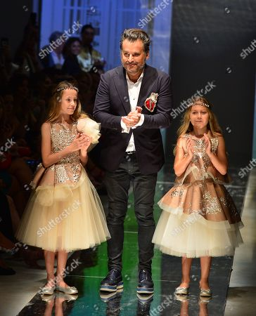 Stock Photo of Oscar Carvallo with models on catwalk