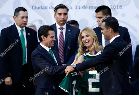 Enrique Pena Nieto, Angelica Rivera, Rafael Marquez. Mexican President Enrique Pena Nieto, front left, and first lady Angelica Rivera are presented with Mexican national soccer team jersey by team captain Rafael Marquez, right, at a ceremony to present the national flag to the Mexico's team ahead of the start of the 2018 World Cup in Russia, at Los Pinos presidential residence in Mexico City