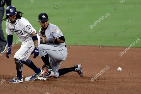 San Diego Padres' Freddy Galvis, left, stands at second and looks at the ball after Miami Marlins second baseman Starlin Castro, right, missed the catch during the fifth inning of a baseball game, in San Diego. Padres' A.J. Ellis was safe at first, Christian Villanueva scored, and Castro picked up an error on the play