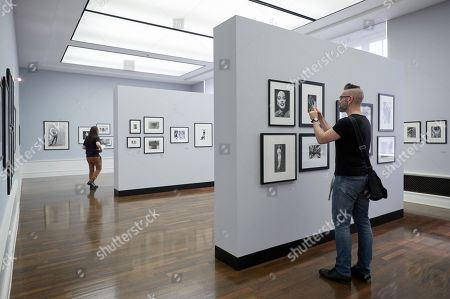 A visitor takes pictures of photographs by Philippe Halsman during a press preview of 'Between Art & Fashion. Photographs from the Collection of Carla Sozzani' at the Helmut Newton Foundation in Berlin, Germany, 01 June 2018. The exhibition runs from 02 June to 18 November.