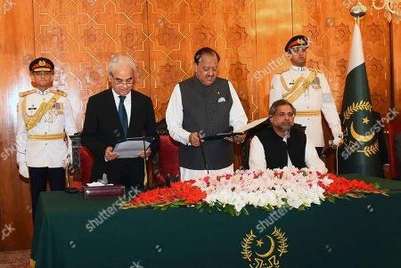 In this photo released by the Press Information Department, President Mamnoon Hussain, center, administers the oath to former Pakistani Chief Justice Nasir-ul-Mulk as Caretaker Prime Minister at the Aiwan-e-Sadr, in Islamabad, Pakistan, . Former Prime Minister Shahid Khaqan Abbasi sits at left