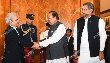 In this photo released by the Press Information Department, President of Pakistan Mamnoon Hussain, center, shakes hands with new Care Taker Prime Minister Nasir-ul-Mulk at the Aiwan-e-Sadr, in Islamabad, Pakistan, . Former Prime Minister Shahid Khaqan Abbasi seen at right