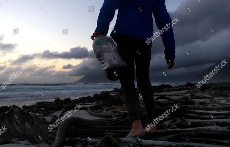 A member of the youth environmental organisation Oceano Reddentes who educate, collect and construct Ecobricks from plastic waste picks plastic off a beach in Cape Town, South Africa, 31 May 2018. Oceano Reddentes teaches ocean users to collect plastic to make the Ecobrick which is then used to build homes for the homeless. Plastic pollution has reached epidemic proportion. According to an Ellen MacArthur Foundation report there will be more plastic in the ocean than fish by 2050. Africa is one of the most affected continents due to its extensive coastline and underdeveloped waste systems allowing plastic waste to easily enter the ocean.  The rapid growth of plastic production in the three biggest areas the European Union, China and the US particularly in single-use plastics is recognised as one of the greatest risks facing the environment and mankind. Efforts at recycling and plastic waste education are on the rise on the African continent with many programs being initiated by youth groups who view the problem as the biggest environmental challenge facing the new generation.
